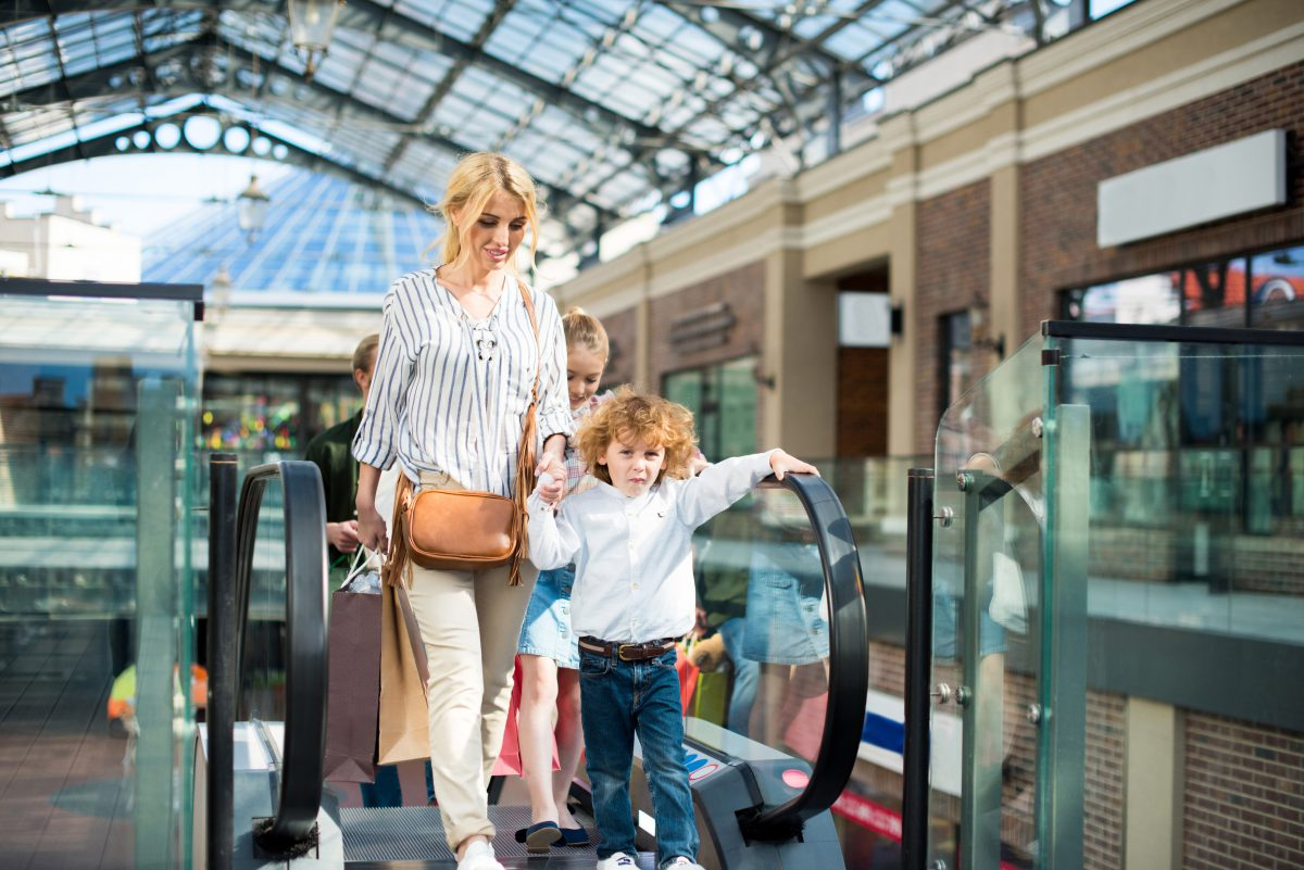 Millennial parent coming up mall escalator with young boy