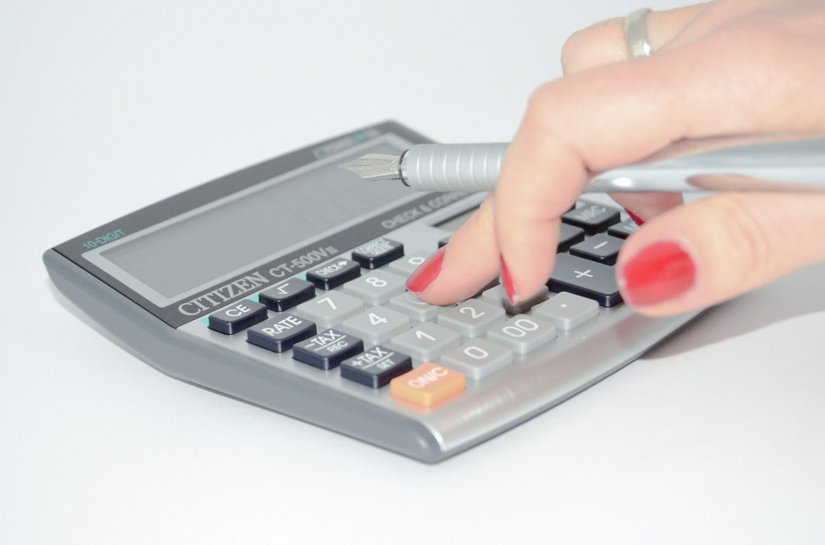 ladies hand typing on calculator