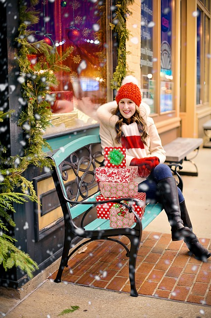 woman-sitting-on-bench-in-snow-at-mall-with-christmas-presents