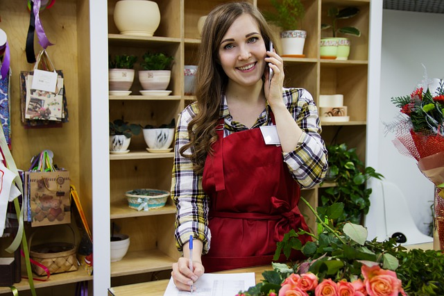 woman wearing red apron taking holiday phone order in flowershop
